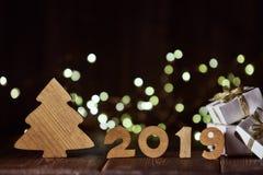 Houten spar, giftvakjes en tekst 2019 van houten cijfer aangaande donkere houten achtergrond met LEIDENE lichte slinger Horizonta royalty-vrije stock afbeelding