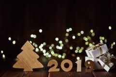 Houten spar, giftvakjes en tekst 2019 van houten cijfer aangaande donkere houten achtergrond met LEIDENE lichte slinger Horizonta stock afbeeldingen