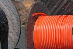 Houten spoelen met zwarte en oranje kabels Stock Afbeeldingen