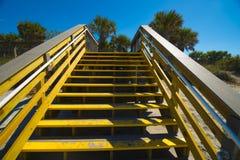 Houten stappen aan het strand en de oceaan die omhoog eruit zien Stock Fotografie