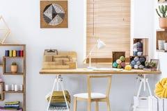 Houten stoel bij bureau met lamp en kleurrijke garens in het binnenland van het huisbureau met affiche Echte foto royalty-vrije stock foto's