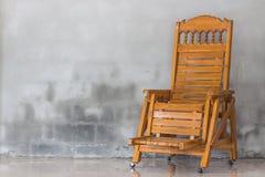 Houten stoel en concrete muur stock foto