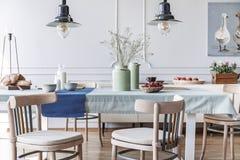Houten stoelen bij lijst in het witte binnenland van de plattelandshuisjeeetkamer met lampen en affiche Echte foto royalty-vrije stock afbeeldingen