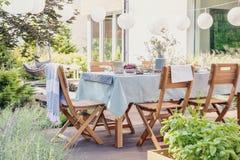 Houten stoelen bij lijst met bloemen en voedsel in de tuin met installaties en lantaarns stock afbeeldingen