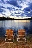 Houten stoelen bij zonsondergang op meerkust royalty-vrije stock afbeeldingen