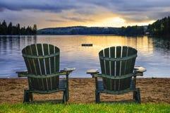 Houten stoelen bij zonsondergang op strand Stock Foto's
