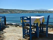 Houten stoelen en lijst in een herberg op de achtergrond van het overzees Stock Foto