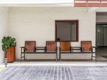 Houten stoelen tegen bakstenen muur stock foto's