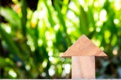 Houten stuk speelgoed als concept van het droomhuis met vage groene achtergrond Royalty-vrije Stock Foto