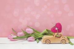 Houten stuk speelgoed auto die een hart en roze tulpen op roze backgrou dragen Royalty-vrije Stock Afbeelding