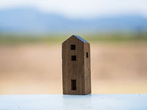 Houten stuk speelgoed huis met onduidelijk beeldachtergrond Stock Foto