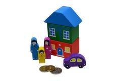 Houten stuk speelgoed mensen, een huis en een auto dichtbij de metaalmuntstukken Geïsoleerd over witte achtergrond Stock Fotografie