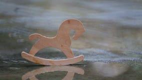 Houten stuk speelgoed paard in een vulklei in de regen stock video