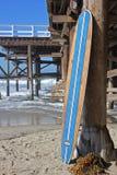 Houten surfplank tegen het strandpijler van Californië Royalty-vrije Stock Afbeeldingen
