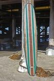 Houten surfplank tegen het strandpijler van Californië Stock Foto's