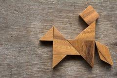 Houten tangram als mensenrit de paardvorm op oud hout backgroun Stock Afbeelding