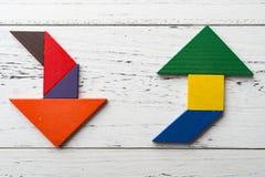 Houten tangram in pijl twee geeft gestalte is omhooggaand en andere is neer stock afbeelding