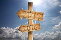 Houten teken van 2016 en 2017 binnen in linkerzijde op blauwe hemelachtergrond Stock Foto's