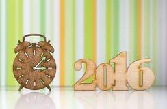 Houten teken van wekker en inschrijving van het jaar van 2016 op groen Stock Afbeeldingen