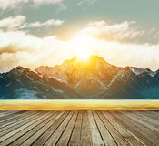 Houten terras en zoet watermeer met zon die achter snowcap toenemen royalty-vrije stock foto's
