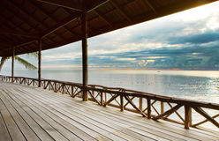 Houten terras in houten pavillion tegen vreedzaam van hemeloverzees Royalty-vrije Stock Afbeeldingen