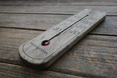 Houten thermometer op oude houten achtergrond Stock Afbeeldingen