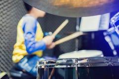 Houten trommelstokken in handen die van Aziatisch jong geitje blauwe en gele t-shirts dragen aan het leren en speldrumstel in muz royalty-vrije stock afbeelding