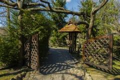 Houten tuinpoorten onder bomengras en mooie die rotsweg met mos en zand wordt behandeld royalty-vrije stock afbeeldingen
