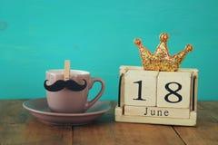 Houten uitstekende kalender achttiende van juni naast kop van koffie en snor Stock Fotografie