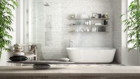Houten uitstekende lijst of plank met steensaldo, over vage uitstekende badkamers met badkuip en douche, feng shui, zen concept A royalty-vrije stock afbeeldingen