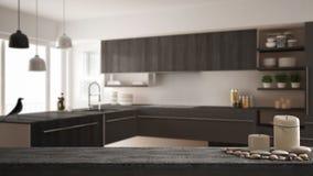Houten uitstekende lijstbovenkant of plank met kaarsen en kiezelstenen, zen stemming, over vage moderne minimalistic keuken, grij royalty-vrije stock foto's