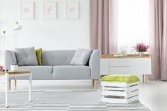 Houten vakje met groen hoofdkussen op gestreept tapijt in heldere Skandinavische woonkamer met grijze echte laag en koffietafel, stock fotografie