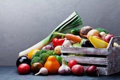 Houten vakje met het landbouwbedrijfgroenten van de de herfstoogst en wortelsgewassen op donkere keukenlijst Gezond en natuurvoed Royalty-vrije Stock Foto