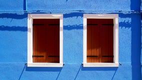 Houten venster met wit kader op het blauwe huis van de kleurenmuur in Burano royalty-vrije stock fotografie