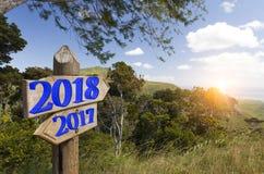 Houten verkeersteken met tekst 2018 en 2017 op een achtergrond van de tropische aard, Beeld voor Nieuw jaar 2018 Concept Stock Fotografie