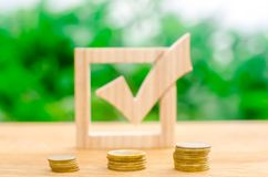 Houten vinkje en stapels muntstukken Rentevoeten op stortingen en leningen Het lobbyen van de goedkeuring van verordeningen en we royalty-vrije stock afbeeldingen
