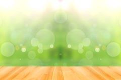 Houten vloer en abstracte groene bokehachtergrond Stock Foto