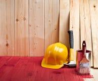 Houten vloer en muur met een borstel, een verf, een hamer en een gele helme stock fotografie