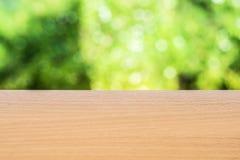 Houten vloer met de achtergrond van de bokehboom in de zomer Het hanteren van het behang of aardfotoconcept Stock Fotografie