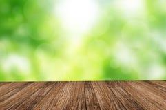 Houten vloer over groene bosbokehachtergrond Stock Foto's
