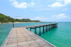 Houten voetgangersbrug over het water dichtbij het strand Stock Fotografie