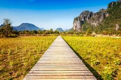 Houten voetpad op een gebied bij zonsondergang Berglandschap, Laos, Stock Fotografie