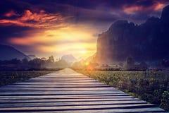 Houten voetpad op een gebied bij zonsondergang Berglandschap, Laos, Royalty-vrije Stock Foto