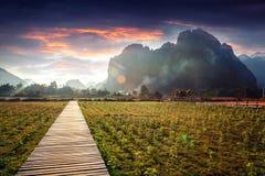Houten voetpad op een gebied bij zonsondergang Berglandschap, Laos, Stock Afbeelding