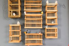 Houten vogel` s kooi op grijze muur zoals decor Stock Afbeelding