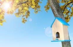 Houten vogelhuis onder de herfstboom op blauwe hemelachtergrond met exemplaarruimte Stock Foto's