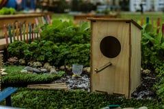 Houten vogelhuis in samenstelling met groene installaties stock fotografie