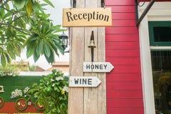 Houten voorzie van ontvangst voor hotel met wijn en honing van wegwijzers royalty-vrije stock afbeelding