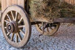 Houten wagen met droog gras Oude kar met houten wielen Traditioneel vervoer op het platteland Historisch rustiek voertuig met dro royalty-vrije stock afbeeldingen