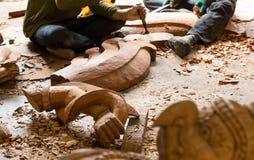 Houten wapen en Garuda-vogelstandbeeld met herstellers die hout voor restauratieprojecten beitelen bij het Heiligdom van Waarheid Stock Foto's